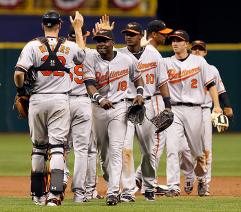 ST. PETERSBURG, FL - APRIL 03:  Outfielders Felix Pie #18 and Adam Jones #10 of the Baltimore Orioles celebrate their team's victory over the Tampa Bay Rays at Tropicana Field on April 3, 2011 in St. Petersburg, Florida.  (Photo by J. Meric/Getty Images)