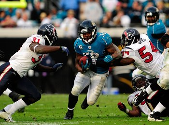 JACKSONVILLE, FL - DECEMBER 06:  Maurice Jones-Drew #32 of the Jacksonville Jaguars attempts to run past  Bernard Pollard #31 of the Houston Texans during the game at Jacksonville Municipal Stadium on December 6, 2009 in Jacksonville, Florida.  (Photo by