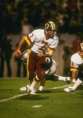 22  Jan 1984:  Quarterback Joe Theismann  #7 of the Washington Redskins charges off with the ball during Super Bowl XVIII against the Los Angeles Raiders at Tampa Stadium in Tampa, Florida.The Raiders won the game, 38-9. Mandatory Credit: Allsport  /Allsp