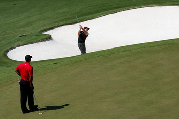 AUGUSTA, GA - APRIL 12:  Phil Mickelson plays a bunker shot on the ninth hole as Tiger Woods looks on during the final round of the 2009 Masters Tournament at Augusta National Golf Club on April 12, 2009 in Augusta, Georgia.  (Photo by David Cannon/Getty