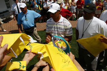 AUGUSTA, GA - APRIL 05:  Tiger Woods signs his autograph for fans as he walks off the practice range during a practice round prior to the 2010 Masters Tournament at Augusta National Golf Club on April 5, 2010 in Augusta, Georgia.  (Photo by Harry How/Gett