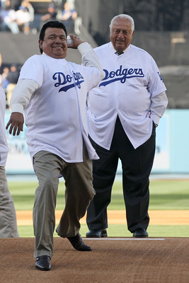 LOS ANGELES, CA - MARCH 31:  Former Los Angeles Dodgers pitcher Fernando Valenzuela throws out the ceremonial first pitch as former Dodger manager Tommy Lasorda looks on prior to the Dodgers playing the San Francisco Giants on Opening Day at Dodger Stadiu