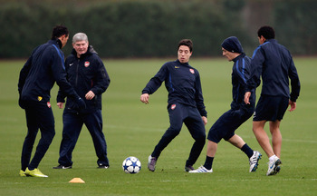 ST ALBANS, ENGLAND - NOVEMBER 22: Samir Nasri (C) is watched by Assistant coach Pat Rice during Arsenal training ahead of their UEFA Champions League match against Braga at London Colney on November 22, 2010 in St Albans, England.  (Photo by Scott Heavey/