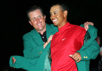 AUGUSTA, GA - APRIL 10:  Tiger Woods smiles as he is presented with the green jacket by Phil Mickelson after Woods won The Masters at the Augusta National Golf Club on April 10, 2005 in Augusta, Georgia.  (Photo by Harry How/Getty Images)