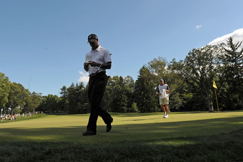 NEWTOWN SQUARE, PA - JULY 01:  Tiger Woods checks his scorecard as he walks off the 14th green ahead of his caddie Steve Williams during the first round of the AT&T National at Aronimink Golf Club on July 1, 2010 in Newtown Square, Pennsylvania.  (Photo b