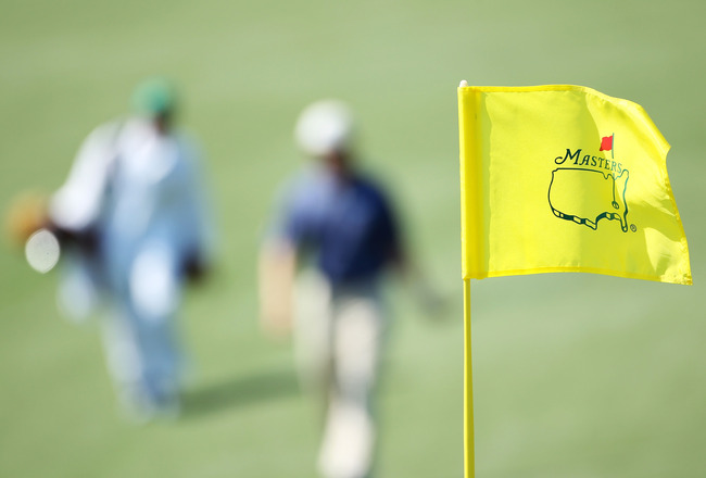 AUGUSTA, GA - APRIL 04:  A Masters flagstick is seen as a player and caddie approach a green during a practice round prior to the 2011 Masters Tournament at Augusta National Golf Club on April 4, 2011 in Augusta, Georgia.  (Photo by Andrew Redington/Getty