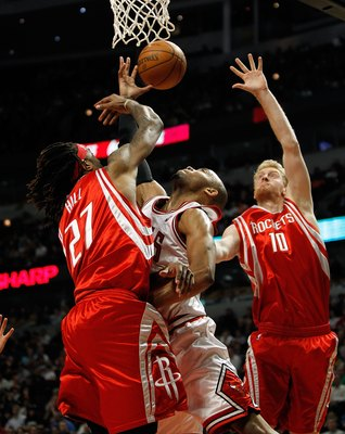 CHICAGO - MARCH 22: Taj Gibson #22 of the Chicago Bulls reaches for a rebound between Jordan Hill #27 and Chase Budinger #10 of the Houston Rockets at the United Center on March 22, 2010 in Chicago, Illinois. The Bulls defeated the Rockets 98-88. NOTE TO