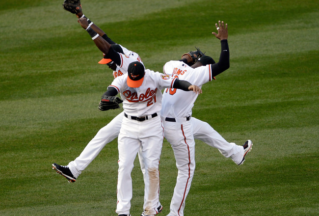 BALTIMORE, MD - APRIL 04: Felix Pie #18 of the Baltimore Orioles (L) and teammates Nick Markakis #21 (C) and Adam Jones #10 celebrate in the outfield after the Orioles defeated the Detroit Tigers 5-1 during opening day at Oriole Park at Camden Yards on Ap