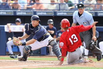 PEORIA, AZ - MARCH 15:  Maicer Izturis #13 of the Los Angeles Angels of Anaheim safely slides into home plate past the tag from catcher Nick Hundley #4 of the San Diego Padres during the third inning of the spring training game at Peoria Stadium on March