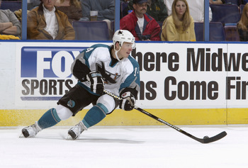 ST. LOUIS - APRIL 12:  Alex Korolyuk #94 of the San Jose Sharks looks up the ice as he circles with the puck against the St. Louis Blues in game three of the Western Conference Quarterfinals on April 12, 2004 at the Savvis Center in St. Louis, Missouri.