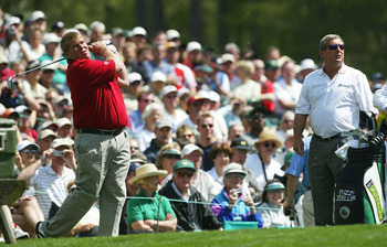 AUGUSTA, GA - APRIL 6:  John Daly of the USA hits a shot on the 12th tee as Fuzzy Zoeller looks on during the second practice day for the Masters at the Augusta National Golf Club on April 6, 2004 in Augusta, Georgia.  (Photo by David Cannon/Getty Images)