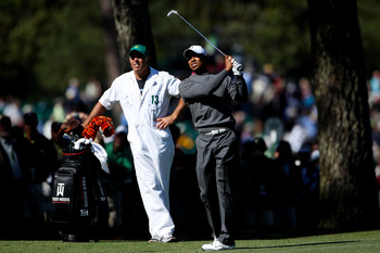 AUGUSTA, GA - APRIL 06:  Tiger Woods hits a shot as his caddie Steve Williams looks on during a practice round prior to the 2011 Masters Tournament at Augusta National Golf Club on April 6, 2011 in Augusta, Georgia.  (Photo by Andrew Redington/Getty Image