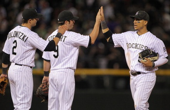 DENVER, CO - APRIL 05:  Troy Tulowitzki #2, Ian Stewart #9 and Carlos Gonzalez #5 of the Colorado Rockies celebrate their victory over the Los Angeles Dodgers at Coors Field on April 5, 2011 in Denver, Colorado. The Rockies defeated the Dodgers 3-0.  (Pho