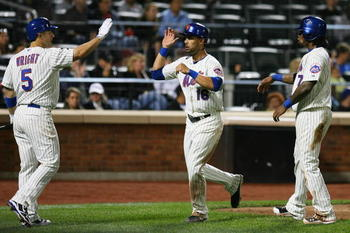 NEW YORK - SEPTEMBER 14: Angel Pagan #16 of the New York Mets is welcomed home by teammates David Wright #5 and Jose Reyes #7 after running in a two-run double hit by Carlos Beltran #15 (not seen) of the Mets in the fourth inning against the Pittsburgh Pi