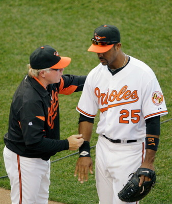 BALTIMORE, MD - APRIL 04: Manager Buck Showalter #26 of the Baltimore Orioles congratulates first baseman Derrek Lee #25 of the Baltimore Orioles after they defeated the Detroit Tigers during opening day at Oriole Park at Camden Yards on April 4, 2011 in