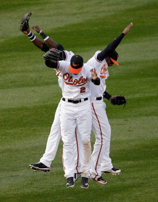 BALTIMORE, MD - APRIL 04:  Felix Pie #18 of the Baltimore Orioles (L) and teammates Nick Markakis #21 (C) and Adam Jones #10 celebrate in the outfield after the Orioles defeated the Detroit Tigers 5-1 during opening day at Oriole Park at Camden Yards on A