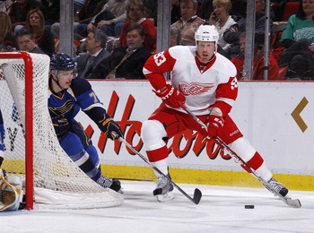 DETROIT, MI - MARCH 30: Johan Franzen #93 of the Detroit Red Wings tries to keep the puck from the stick of Adam Cracknell #79 of the St. Louis Blues at Joe Louis Arena on March 30, 2011 in Detroit, Michigan.  (Photo by Gregory Shamus/Getty Images)