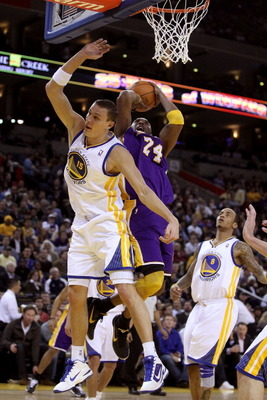 OAKLAND, CA - JANUARY 12: Kobe Bryant #24 of the Los Angeles Lakers is fouled by Andris Biedrins #15 of the Golden State Warriors at Oracle Arena on January 12, 2011 in Oakland, California. NOTE TO USER: User expressly acknowledges and agrees that, by dow