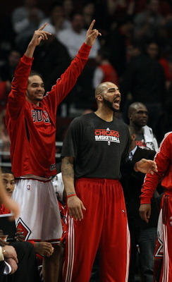 CHICAGO, IL - MARCH 21: Joakim Noah #13 (L) and Carlos Boozer #5 of the Chicago Bulls encourage teammates playing against the Sacramento Kings from the bench at the United Center on March 21, 2011 in Chicago, Illinois. The Bulls defeated the Kings 132-92.