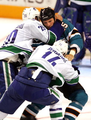 SAN JOSE, CA - SEPTEMBER 18:  Dave Scatchard #20 and Alexandre Burrows #14 of the Vancouver Canucks and Jody Shelley #45 of the San Jose Sharks get in a fight during their preseason game at HP Pavilion on September 18, 2009 in San Jose, California.  (Phot