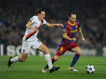 BARCELONA, SPAIN - APRIL 06:  Andres Iniesta (R) of Barcelona runs for the ball with Mykola Ishchenko of Shakhtar Donetsk during the UEFA Champions League quarter final first leg match between Barcelona and Shakhtar Donetsk at the Camp Nou stadium on Apri