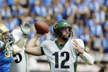 PASADENA, CA - OCTOBER 12:  Quarterback Jason Fife #12 of the Oregon Ducks throws the ball under pressure during the NCAA football game against the UCLA Bruins at the Rose Bowl on October 12, 2002 in Pasadena, California.  Oregon defeated UCLA 31-30.  (Ph