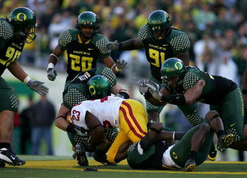 EUGENE, OR - OCTOBER 27:  Chauncey Washington #23 of the Southern California Trojans is tackled by the Oregon Ducks at Autzen Stadium October 27, 2007 in Eugene, Oregon.  (Photo by Jonathan Ferrey/Getty Images)