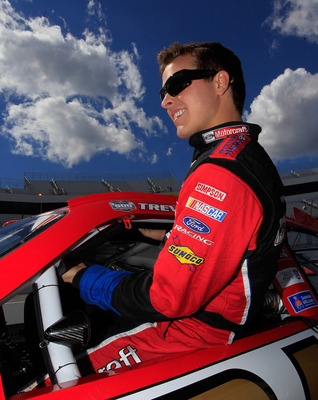 MARTINSVILLE, VA - APRIL 02:  Trevor Bayne, driver of the #21 Motorcraft/Quick Lane Tire & Auto Center Ford, climbs in his car on the grid during qualifying for the NASCAR Sprint Cup Series Goody's Fast Relief 500 at Martinsville Speedway on April 2, 2011
