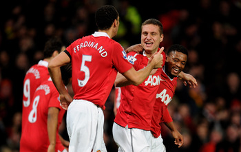 MANCHESTER, ENGLAND - FEBRUARY 01:  Nemanja Vidic of Manchester United celebrates scoring his team's third goal with team mates Rio Ferdinand and Patrice Evra (R) during the Barclays Premier League match between Manchester United and Aston Villa at Old Tr
