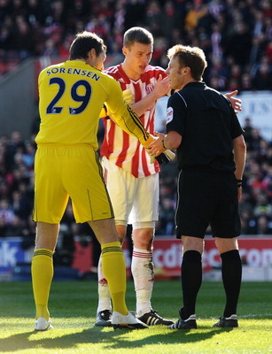 STOKE ON TRENT, ENGLAND - MARCH 13:  Referee Mike Jones is confronted by Ryan Shawcross of Stoke City and goalkeeper Thomas Sorensen of Stoke City after allowing the opening West Ham United goal during the FA Cup sponsored by E.ON 6th Round match between