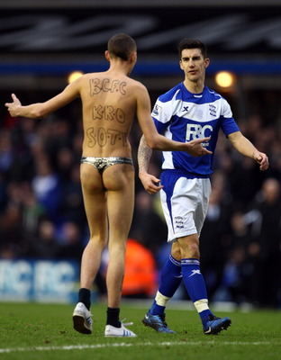 BIRMINGHAM, ENGLAND - JANUARY 16:  Liam Ridgewell of Birmingham tells a streaker to leave the pitch during the Barclays Premier League match between Birmingham City and Aston Villa at St.Andrews on January 16, 2011 in Birmingham, England.  (Photo by Richa