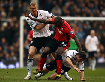 LONDON, ENGLAND - MARCH 05:  Jason Roberts of Blackburn tussles with Brede Hangeland and Aaron Hughes of Fulham during the Barclays Premier League match between Fulham and Blackburn Rovers at Craven Cottage on March 5, 2011 in London, England.  (Photo by