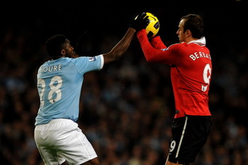MANCHESTER, UNITED KINGDOM - NOVEMBER 10:   Kolo Toure of Manchester City tries to grab the ball from Dimitar Berbatov of Manchester United during the Barclays Premier League match between Manchester City and Manchester United at the City of Manchester St