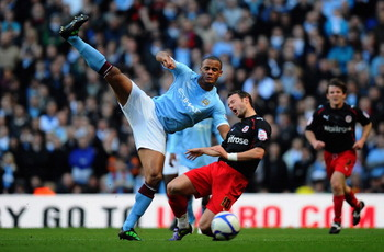 MANCHESTER, ENGLAND - MARCH 13:  Vincent Kompany of Manchester City tackles Noel Hunt of Reading during the FA Cup sponsored by E.On Sixth Round match between Manchester City and Reading at the City of Manchester Stadium on March 13, 2011 in Manchester, E