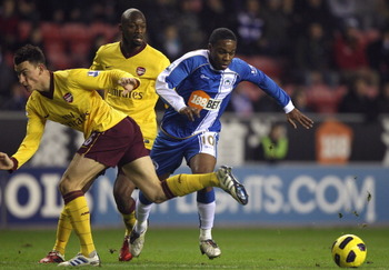 WIGAN, ENGLAND - DECEMBER 29:  Charles N'Zogbia (R) of Wigan Athletic is brought down by Laurent Koscielny of Arsenal to concede a penalty during the Barclays Premier League match between Wigan Athletic and Arsenal at DW Stadium on December 29, 2010 in Wi
