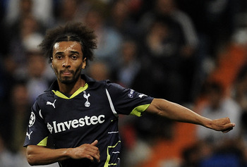 MADRID, SPAIN - APRIL 05:  Benoit Assou-Ekotto of Tottenham Hotspur (R) makes a pass under a challenge by Xabi Alonso of Real Madrid during the UEFA Champions League quarter final first leg match between Real Madrid and Tottenham Hotspur at Estadio Santia
