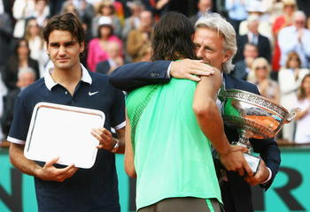 PARIS - JUNE 08:  Rafael Nadal of Spain receives the trophy from Bjorn Borg, as runner up Roger Federer (L) of Switzerland looks on after the Men's Singles Final match on day fifteen of the French Open at Roland Garros on June 8, 2008 in Paris, France.  (
