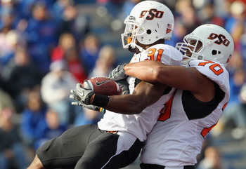 LAWRENCE, KS - NOVEMBER 20:  Jeremy Smith #31 of the Oklahoma State Cowboys is congratulated by Jonathan Rush #70 after a touchdown during the game against the Kansas Jayhawks on November 20, 2010 at Memorial Stadium in Lawrence, Kansas.  (Photo by Jamie