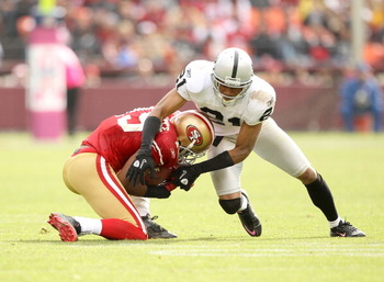 SAN FRANCISCO - OCTOBER 17:  Nnamdi Asomugha #21 of the Oakland Raiders tackles Michael Crabtree #15 of the San Francisco 49ers at Candlestick Park on October 17, 2010 in San Francisco, California.  (Photo by Ezra Shaw/Getty Images)