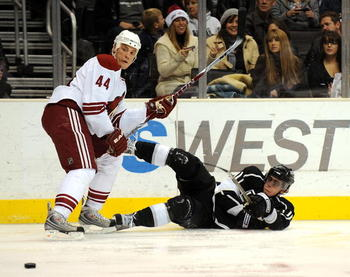 LOS ANGELES, CA - DECEMBER 26:  Anze Kopitarl #11 of the Los Angeles Kings shoots the puck as he falls to the ice in front of Kurt Sauer #44 of the Phoenix Coyotes during the second period at the Staples Center on December 26, 2008 in Los Angeles, Califor