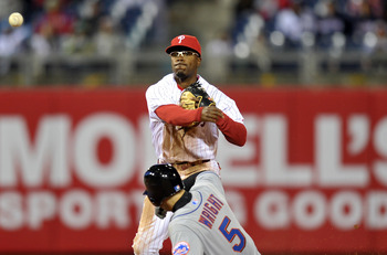 PHILADELPHIA, PA - APRIL 05: Jimmy Rollins #11 of the Philadelphia Phillies makes a throw to first for a double play after getting David Wright #5 of the New York Mets out at second base at Citizens Bank Park on April 5, 2011 in Philadelphia, Pennsylvania