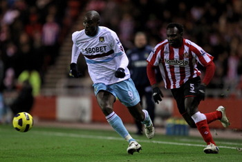 SUNDERLAND, ENGLAND - DECEMBER 05:  Carlton Cole of West Ham United is pursued by John Mensah of Sunderland during the Barclays Premier League match between Sunderland and West Ham United at the Stadium of Light on December 5, 2010 in Sunderland, England.