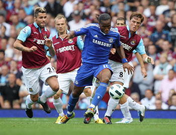 LONDON, ENGLAND - SEPTEMBER 11:  Didier Drogba of Chelsea evades Scott Parker (8) and Valon Behrami of West Ham United (L) during the Barclays Premier League match between West Ham United and Chelsea at the Boleyn Ground on September 11, 2010 in London, E