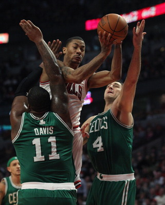 CHICAGO, IL - APRIL 07: Derrick Rose #1 of the Chicago Bulls is called for a charge as he attempts to drive against Glen Davis #11 and Nenad Krstic #4 of the Boston Celtics at United Center on April 7, 2011 in Chicago, Illinois. The Bulls defeated the Cel