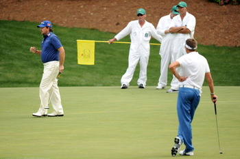 AUGUSTA, GA - APRIL 08:  Graeme McDowell of Northern Ireland watches a putt as Robert Allenby of Australia  looks on during the second round of the 2011 Masters Tournament at Augusta National Golf Club on April 8, 2011 in Augusta, Georgia.  (Photo by Harr