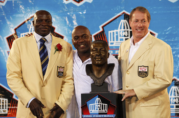 CANTON, OH - AUGUST 8: Bruce Smith looks on with former Buffalo Bills teammates Thurman Thomas (center) and Jim Kelly following his induction into the Pro Football Hall of Fame during the 2009 enshrinement ceremony at Fawcett Stadium on August 8, 2009 in