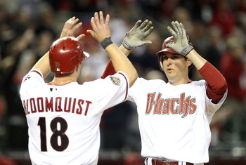 PHOENIX, AZ - APRIL 08:  Kelly Johnson #2 of the Arizona Diamondbacks high fives teammate Willie Bloomquist #18 after Johnson hit a 3 run home run against the Cincinnati Reds during the eighth inning of the Major League Baseball home opening game at Chase