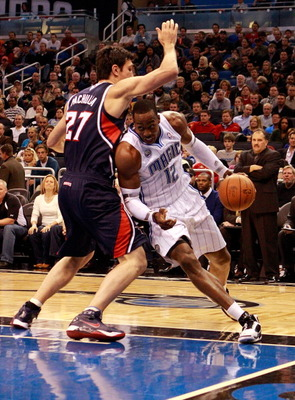 ORLANDO, FL - DECEMBER 06:  Dwight Howard #12 of the Orlando Magic drives against Zaza Pachulia #27 of the Atlanta Hawks during the game at Amway Arena on December 6, 2010 in Orlando, Florida. NOTE TO USER: User expressly acknowledges and agrees that, by