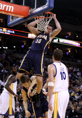 OAKLAND, CA - JANUARY 19:  Tyler Hansbrough #50 of the Indiana Pacers hangs on the rim after he dunked the ball so he doesn't land on Mike Dunleavy #17 during their game against the Golden State Warriors at Oracle Arena on January 19, 2011 in Oakland, Cal