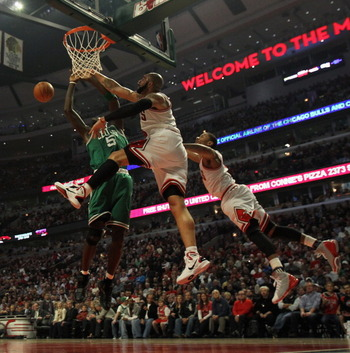 CHICAGO, IL - APRIL 07: Derrick Rose #1 (R) and Carlos Boozer #5 of the Chicago Bulls leap to block a shot by Kevin Garnett #5 of the Boston Celtics at United Center on April 7, 2011 in Chicago, Illinois. NOTE TO USER: User expressly acknowledges and agre